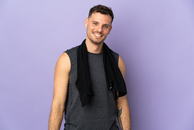 Young caucasian handsome man on purple with sport towel