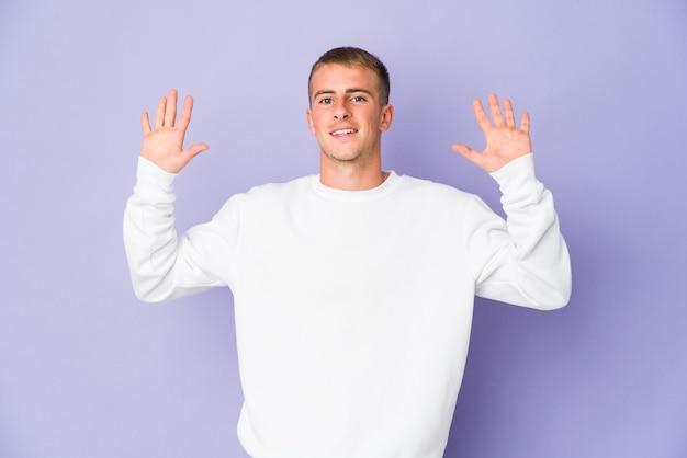 嬉しい驚きを受け取り、興奮して手を上げる若い白人ハンサムな男。