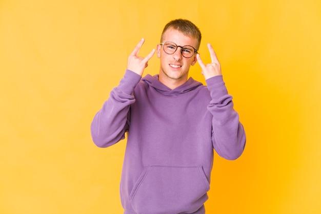 革命の概念として角のジェスチャーを示す若い白人ハンサムな男。