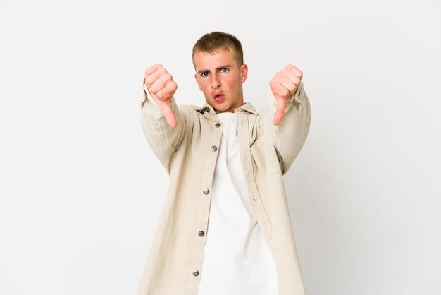 親指を下に向けて嫌悪感を表現する若い白人ハンサムな男。