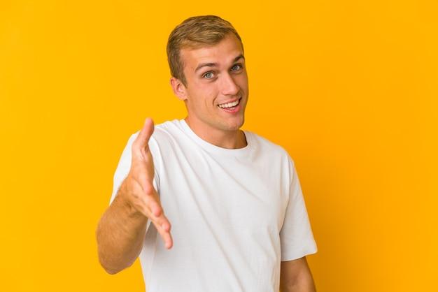 挨拶のジェスチャーでカメラに手を伸ばす若い白人ハンサムな男。