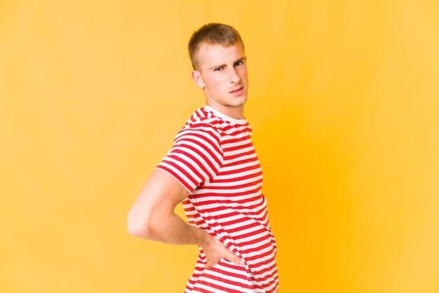 허리 통증을 앓고 젊은 백인 잘 생긴 남자.
