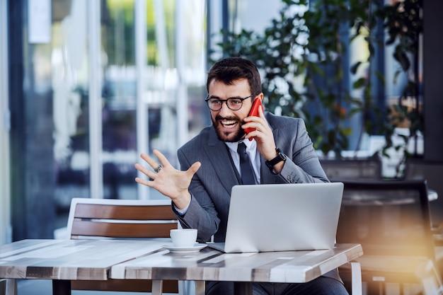 젊은 백인 행복 수염 된 사업가 양복과 안경 카페에 앉아있는 동안 스마트 폰을 통해 전화를 데. 테이블에는 커피와 노트북이 있습니다.