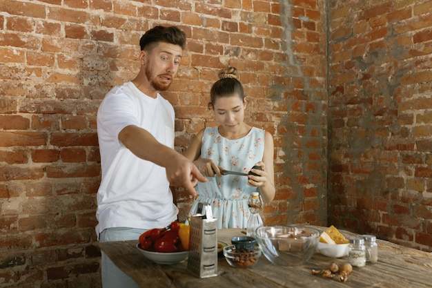 Young caucasian happy couple cooking together using vegetables, cheese, eggs and nuts in recipe against brick wall in their kitchen. nutrition, healthy food, family, relations, domestic life concept.