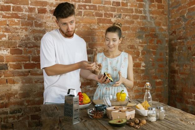 Giovani coppie felici caucasiche che cucinano insieme usando verdure, formaggio, uova e noci nella ricetta contro il muro di mattoni nella loro cucina. nutrizione, cibo sano, famiglia, relazioni, concetto di vita domestica.