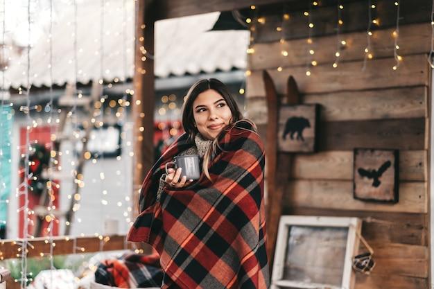 格子縞の若い白人の幸せな女性は、クリスマスの朝を楽しんで、裏庭で温かい飲み物を飲んでいます。