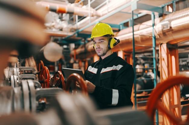 Молодой кавказский трудолюбивый работник тяжелой промышленности в защитном костюме и шлеме используя таблетку и привинчивая клапан.