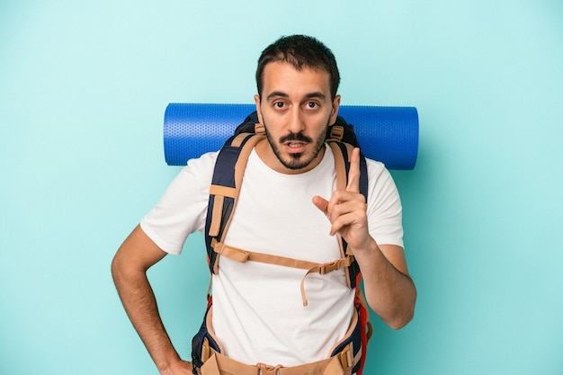Young caucasian hiker man isolated on blue background having an idea, inspiration concept.