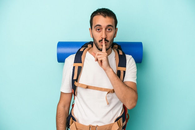 Young caucasian hiker man isolated on blue background keeping a secret or asking for silence.