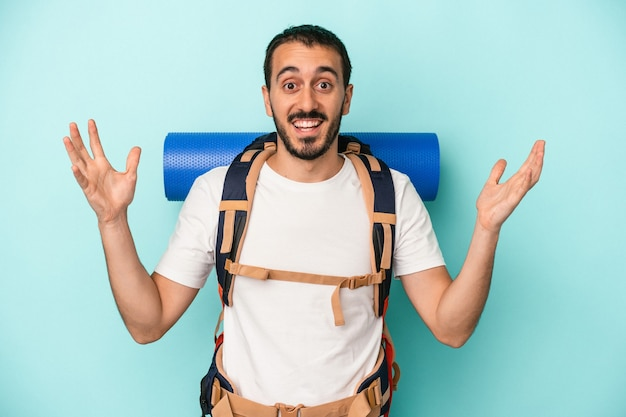 Young caucasian hiker man isolated on blue background receiving a pleasant surprise, excited and raising hands.