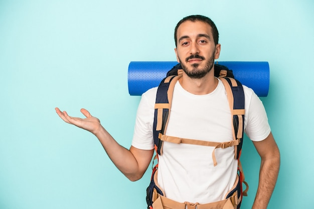 Young caucasian hiker man isolated on blue background showing a copy space on a palm and holding another hand on waist.
