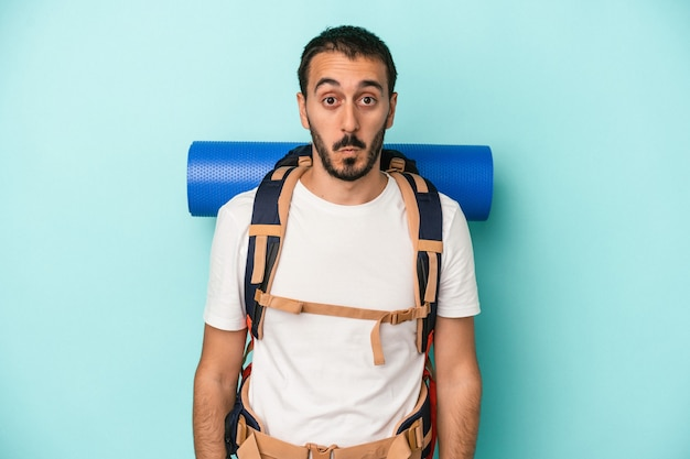 Young caucasian hiker man isolated on blue background shrugs shoulders and open eyes confused.