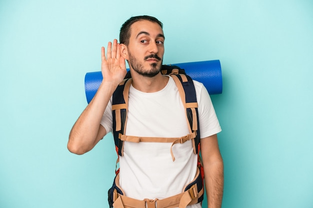 Young caucasian hiker man isolated on blue background trying to listening a gossip.
