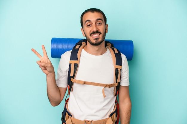 青の背景に孤立した若い白人ハイカーの男は、指で平和のシンボルを示して楽しくてのんきです。