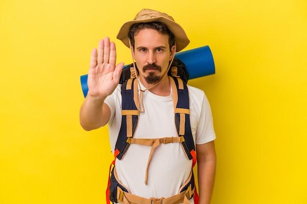 黄色の背景に孤立した若い白人ハイカーの男は、一時停止の標識を示している手を伸ばして立って、あなたを妨げています。