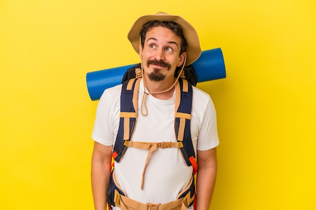Young caucasian hiker man isolated on yellow background dreaming of achieving goals and purposes