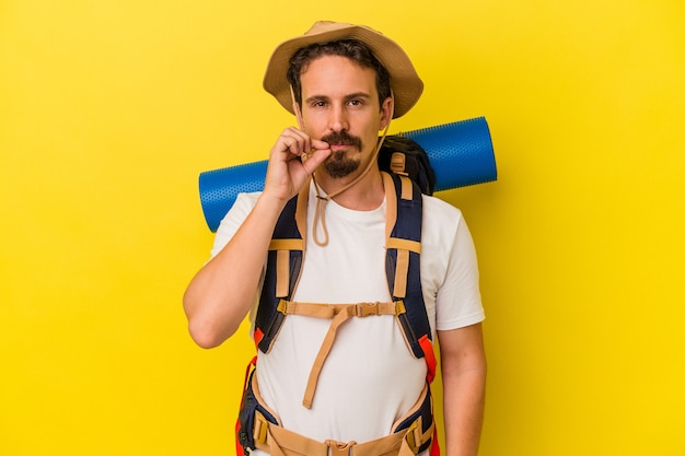 Young caucasian hiker man isolated on yellow background with fingers on lips keeping a secret.