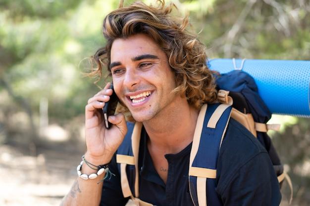 그들의 캠핑 휴가를 보내고 그의 친구에게 전화를하는 젊은 백인 등산객 남자