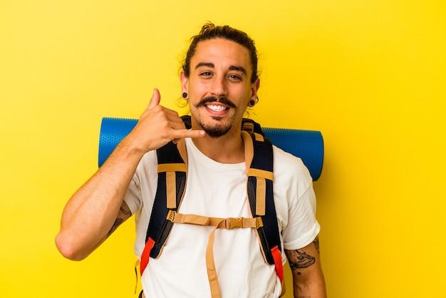 指で携帯電話の呼び出しのジェスチャーを示す黄色の背景に分離された長い髪の若い白人ハイカー男。