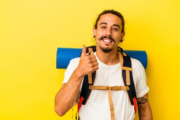 笑みを浮かべて、親指を上げる黄色の背景に分離された長い髪の若い白人ハイカー男