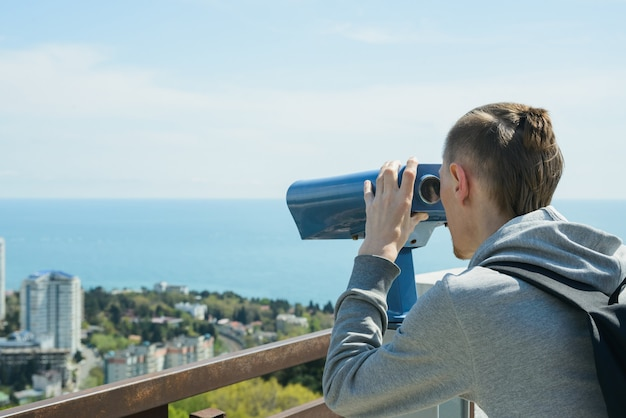 Young caucasian hipster man looking through stationary binoculars at sea and city on observation deck.