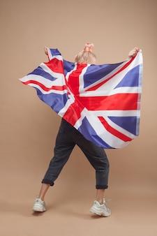 イギリスの旗を持つ若い白人ヒップスターの女性