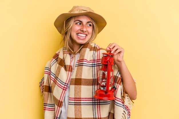Young caucasian holding lantern isolated on yellow background  looks aside smiling, cheerful and pleasant.