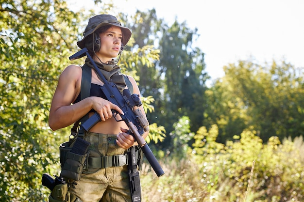 Young caucasian hunter woman in top with a gun during the hunt in search of wild birds