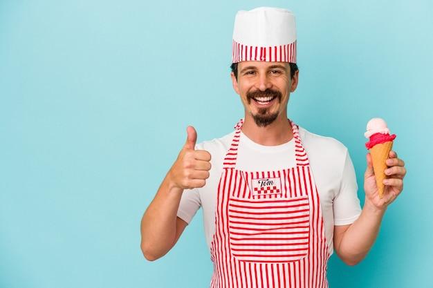 青い背景に分離されたアイスクリームを持って笑顔で親指を上げる若い白人アイスクリームメーカー