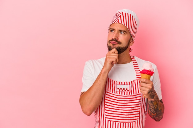 疑わしいと懐疑的な表現で横向きにピンクの背景に分離されたアイスクリームを保持している入れ墨を持つ若い白人製氷機の男。