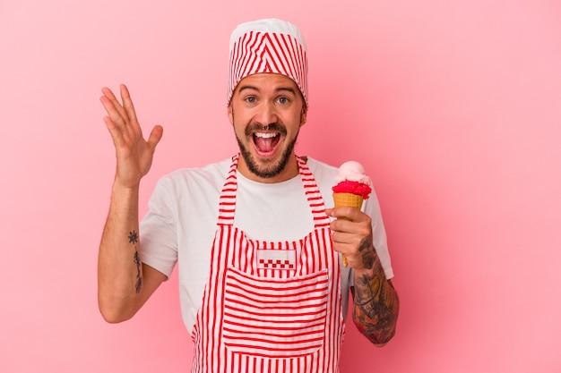 ピンクの背景に分離されたアイスクリームを保持している入れ墨を持つ若い白人製氷機の男は、嬉しい驚きを受け取り、興奮し、手を上げます。
