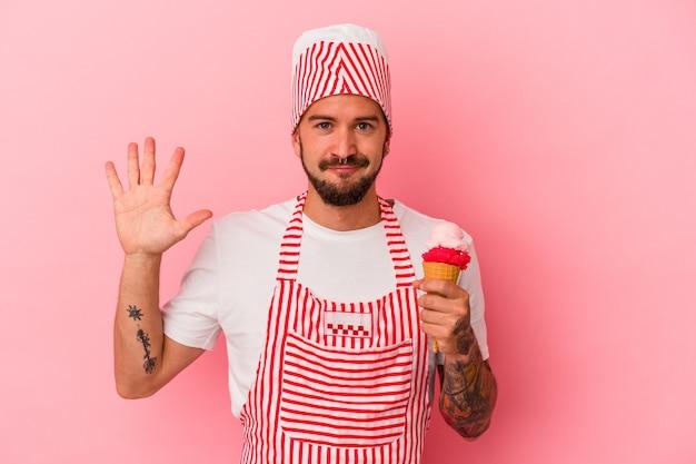 ピンクの背景に分離されたアイスクリームを保持している入れ墨を持つ若い白人製氷機の男は、指で5番目を示して陽気に笑っています。