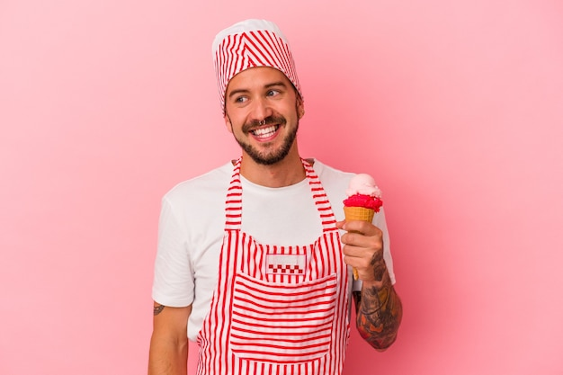 Young caucasian ice maker man with tattoos holding ice cream isolated on pink background  looks aside smiling, cheerful and pleasant.