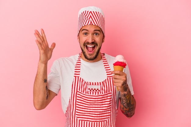 Young caucasian ice maker man with tattoos holding ice cream isolated on pink background  receiving a pleasant surprise, excited and raising hands.