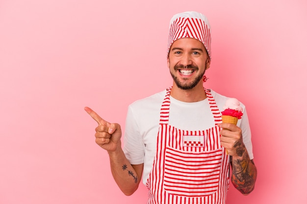 Young caucasian ice maker man with tattoos holding ice cream isolated on pink background  smiling and pointing aside, showing something at blank space.