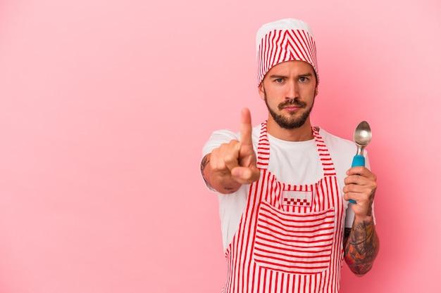 ピンクの背景に分離されたスプーンを保持している入れ墨を持つ若い白人製氷機の男は、指でナンバーワンを示しています。