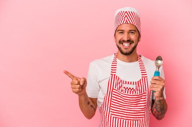 ピンクの背景に分離されたスプーンを保持している入れ墨を持つ若い白人の製氷機の男は、笑顔で脇を指して、空白のスペースで何かを示しています。