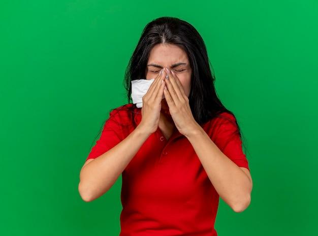 Молодая кавказская больная девушка держит салфетку, держа руки на носу и чихает, изолирована на зеленой стене с копией пространства