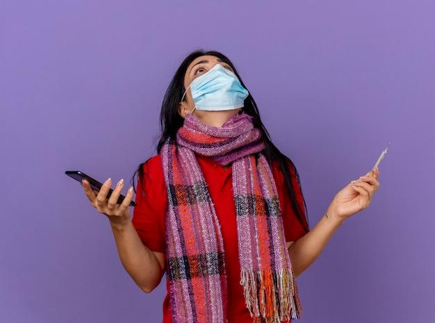 Молодая кавказская больная девушка в маске и шарфе держит мобильный телефон и термометр, глядя вверх, молясь богу, изолированную на фиолетовой стене