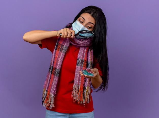 Молодая кавказская больная девушка в маске и шарфе держит пачки капсул, глядя на них через увеличительное стекло, изолированное на фиолетовой стене с копией пространства