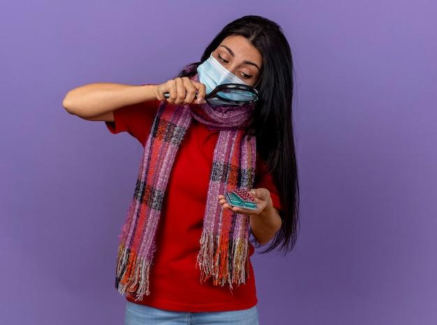 Giovane ragazza malata caucasica che indossa maschera e sciarpa che tengono i pacchetti di capsule guardandoli attraverso la lente di ingrandimento isolata sulla parete viola con lo spazio della copia