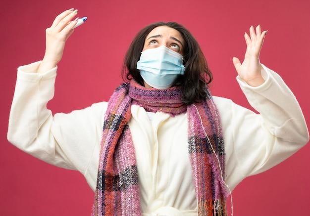 Giovane ragazza malata caucasica che indossa veste e sciarpa con maschera che tiene termometro alzando la mano alzando lo sguardo pregando e benedicendo dio isolato sulla parete cremisi