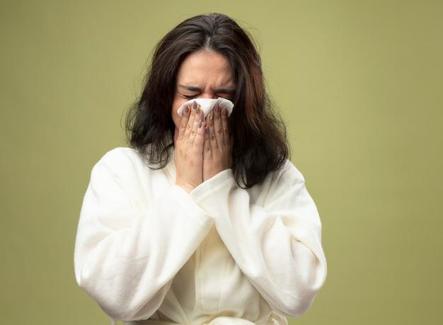 Молодая кавказская больная девушка в халате, вытирая нос салфеткой с закрытыми глазами, изолирована на оливково-зеленом фоне