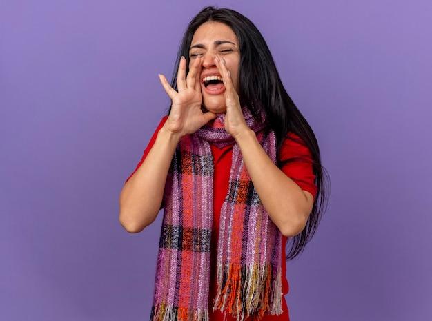 スカーフを身に着けている若い白人の病気の少女は、コピースペースのある紫色の壁に隔離された目を閉じて誰かに大声で叫んで口の近くに手を保ちます