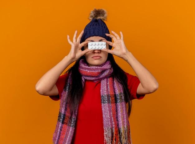 Giovane ragazza malata caucasica che indossa cappello invernale e sciarpa che tiene il pacchetto di compresse davanti agli occhi isolati sulla parete arancione