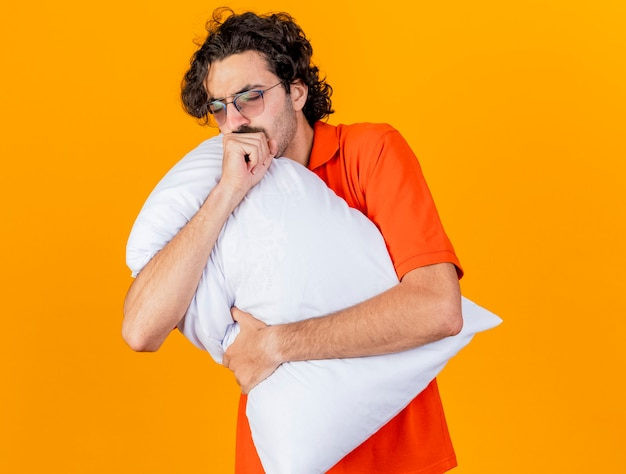 Giovane uomo malato caucasico con gli occhiali che abbraccia cuscino e tosse con gli occhi chiusi isolati su priorità bassa arancione con lo spazio della copia