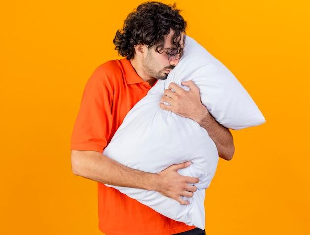 Giovane uomo malato caucasico con gli occhiali che abbraccia il cuscino che tocca il fronte con gli occhi chiusi isolati su fondo arancio con lo spazio della copia