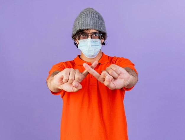 コピースペースで紫色の壁に分離されたジェスチャーをしない眼鏡マスクと冬の帽子を身に着けている若い白人の病気の男