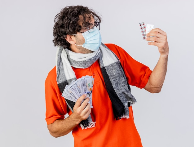 白い背景で隔離の医療ピルを見てお金と医療ピルを保持しているメガネスカーフとマスクを身に着けている若い白人の病気の男