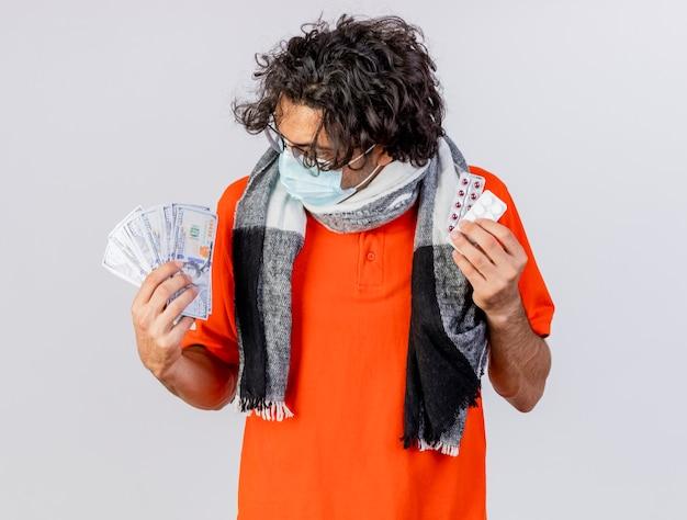 Giovane uomo malato caucasico indossando occhiali sciarpa e maschera che tiene soldi e pillole mediche guardando soldi isolati su sfondo bianco
